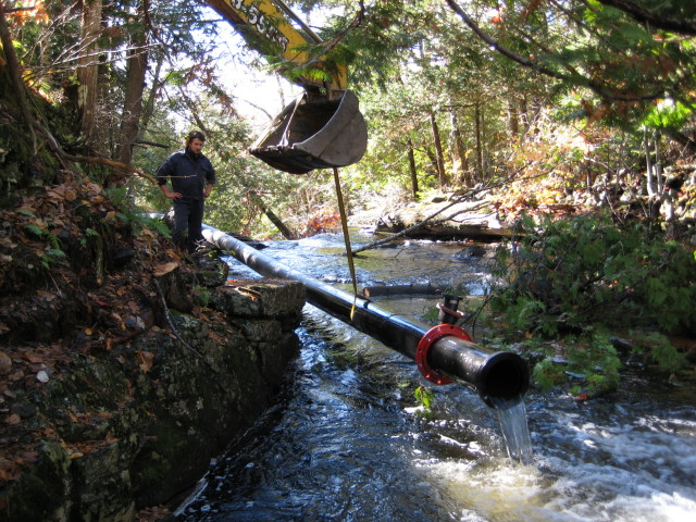 Dragging pipe up the waterfall