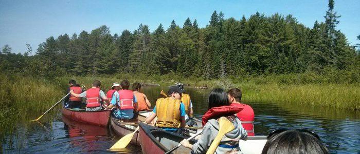 Photo of a Dozen Kids Canoeing During a Field Trip Near Toronto