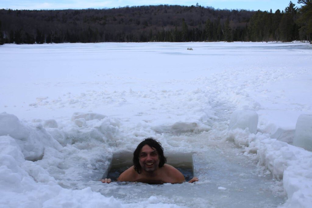 """Photo of a Man Braving the """"Polar Bear Dip."""" Check Out Our Winter Bucket List!"""